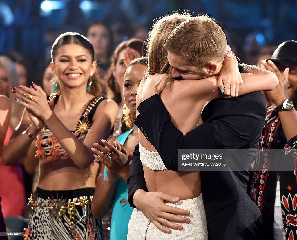 Musician Taylor Swift embraces musician Calvin Harris after winning the Top Artist award as actresssinger Zendaya looks on at the 2015 Billboard...