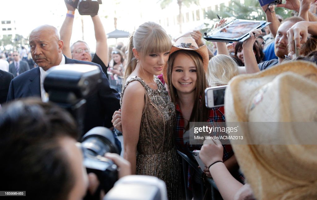 Musician <a gi-track='captionPersonalityLinkClicked' href=/galleries/search?phrase=Taylor+Swift&family=editorial&specificpeople=619504 ng-click='$event.stopPropagation()'>Taylor Swift</a> (L) poses with a fan at the 48th Annual Academy of Country Music Awards at the MGM Grand Garden Arena on April 7, 2013 in Las Vegas, Nevada.