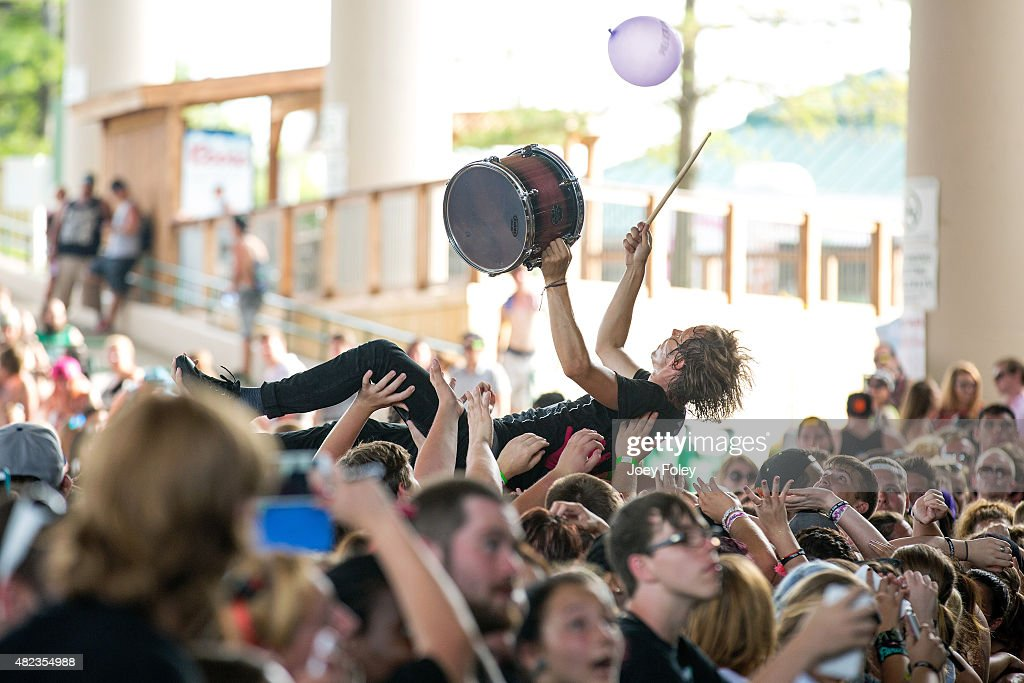 Musician Thomas Becker of Beautiful Bodies playing a drum while crowd surfing on the top of the crowd as he performs live at Klipsch Music Center on...
