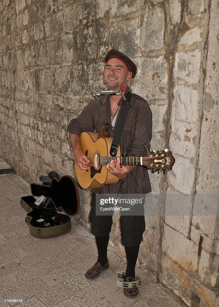 Musician wearing a medieval costume plays guitar for touristsin the UNESCO World Heritage Site city of Dubrovnik on the Dalmatian coast of the Adriatic Sea on May 13, 2011 in Dubrovnik, Croatia. The old town is surrounded by a 1,9 km long city wall and called the Pearl of the Adriatic.