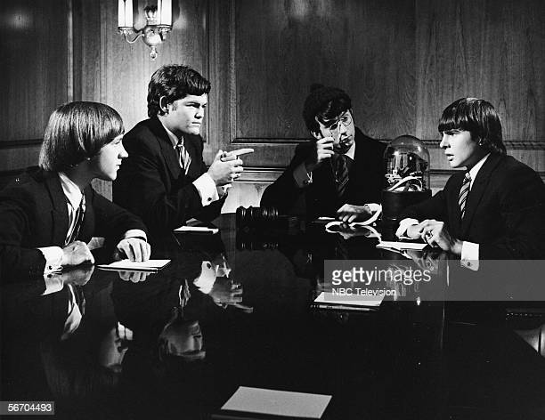Musician/actors the Monkees all dressed in suits sit around a board room table equipped with a stook ticker in a scene from the television show 'The...