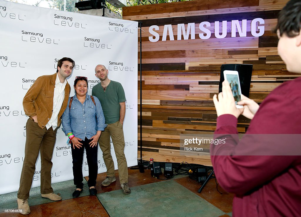 Musicians Ben Schneider and Mark Barry of Lord Huron pose with a fan during the Lord Huron album listening session at the Samsung Studio at SXSW 2015...