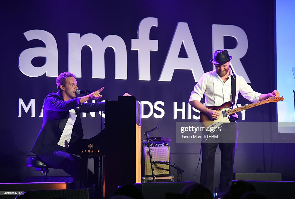 Musicians Chris Martin and Jonny Buckland of Coldplay perform at amfAR LA Inspiration Gala honoring Tom Ford at Milk Studios on October 29 2014 in...