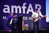 Musicians Chris Martin and Jonny Buckland of Coldplay perform at amfAR LA Inspiration Gala honoring Tom Ford at Milk Studios on October 29 2014 in...