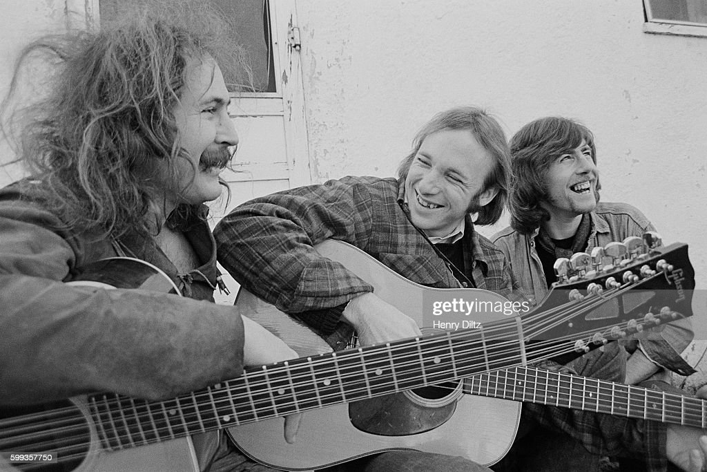 Musicians David Crosby (left), Stephen Stills (center), and Graham Nash play their guitars and relax on a porch.
