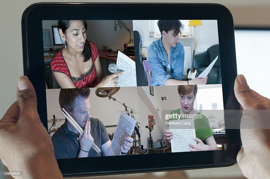 4 musicians discussing online, displayed on tablet : Stock Photo