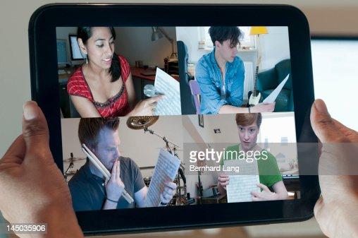 4 musicians discussing online, displayed on tablet : Foto de stock