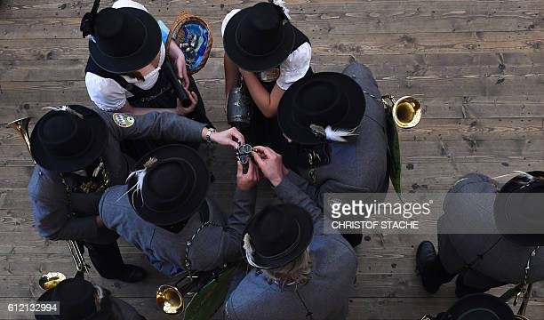 Musicians dressed in typical Bavarian clothes clink glasses in a festival tent prior the traditional riflemen salute shooting on the steps of the...
