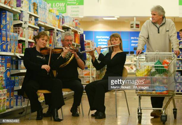 Musicians from left Frances Pye David Garbutt and Rachel Lyons perform to shopper Mike Owen in the ASDA supermarket at Harpurhey North Manchester *...