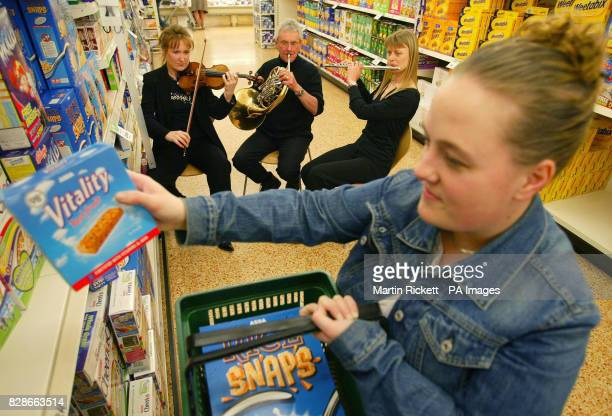 Musicians from left Frances Pye David Garbutt and Rachel Lyons perform to shopper Claire Slater in the ASDA supermarket at Harpurhey North Manchester...