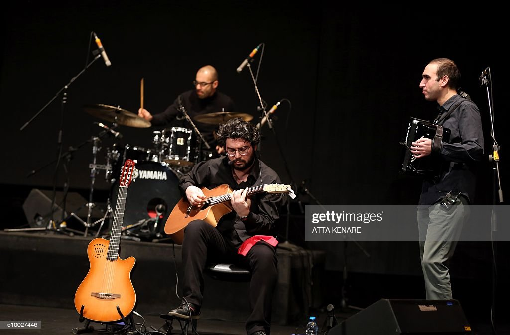 Musicians for Iranian pop singer Omid Nemati perform on stage during the 31th Fajr International Music Festival in the capital Tehran, on February 13, 2016. / AFP / ATTA KENARE
