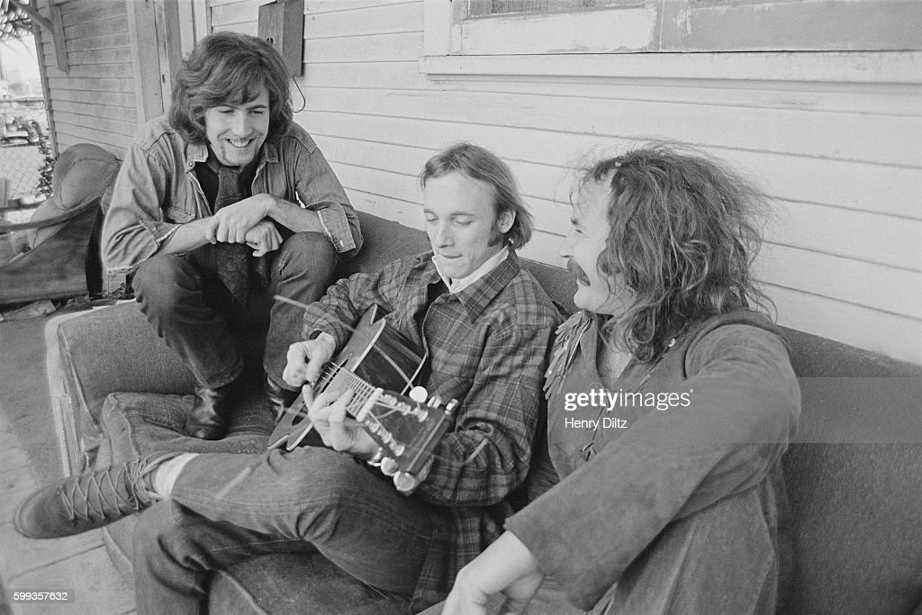Musicians Graham Nash (left), Stephen Stills (center) and David Crosby on a couch outside a house.