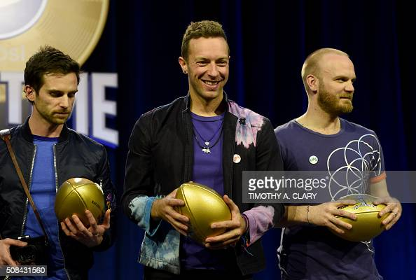 Musicians Guy Berryman Chris Martin and Will Champion of Coldplay pose with footballs at the Pepsi Super Bowl Halftime Press Conference on February 4...