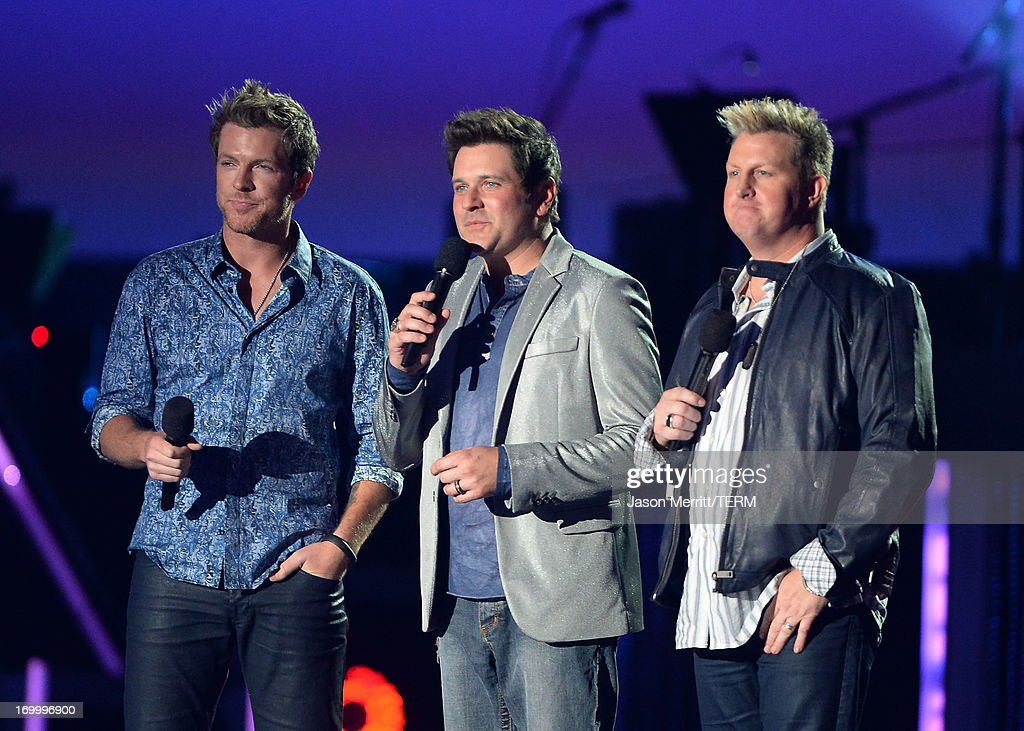 Musicians Joe Don Rooney, Jay DeMarcus and Gary LeVox of Rascal Flatts speak onstage during the 2013 CMT Music awards at the Bridgestone Arena on June 5, 2013 in Nashville, Tennessee.