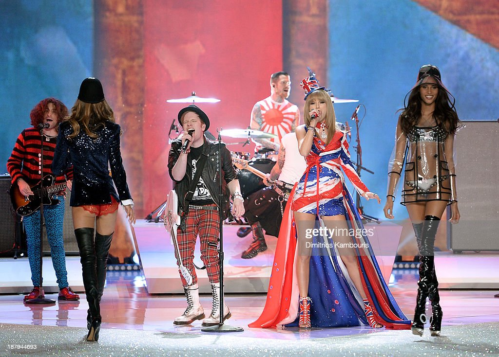 Musicians Joe Trohman, Patrick Stump, Andy Hurley, and Pete Wentz of the band Fall Out Boy and Taylor Swift perform and models Kasi Struss and Cindy Bruna walk the runway at the 2013 Victoria's Secret Fashion Show at Lexington Avenue Armory on November 13, 2013 in New York City.