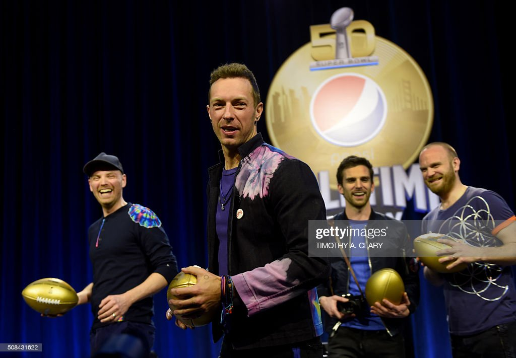 Musicians Jonny Buckland Chris Martin Guy Berrymanand Will Champion of Coldplay pose with footballs at the Pepsi Super Bowl Halftime Press Conference...