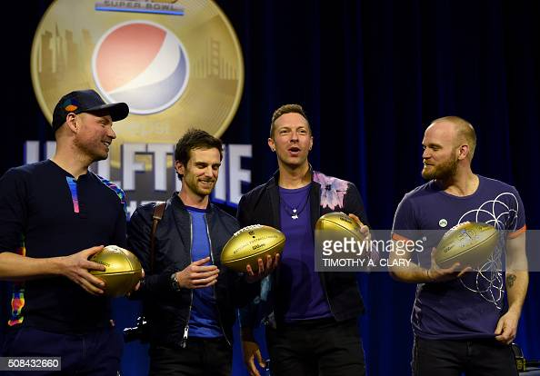 Musicians Jonny Buckland Guy Berryman Chris Martin and Will Champion Coldplay pose with footballs at the Pepsi Super Bowl Halftime Press Conference...