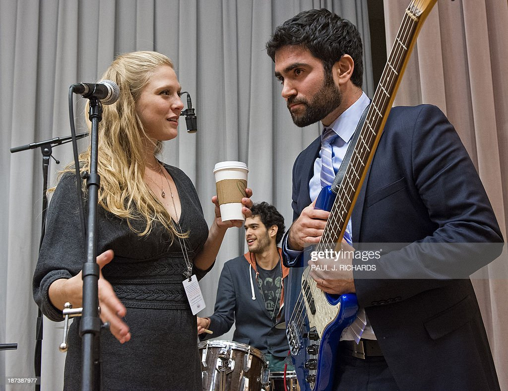 Musicians Kela Sappir(L) and Aaron Sheyer talk during rehearsal, with drummer Ziv Yamin to the rear as their unique band 'Heartbeat' prepares to perform November 8, 2013 inside the US Department of State in Washington. The Jerusalem-based band unites Israeli and Palestinian youth musicians and are starting their second US tour to build understanding. AFP PHOTO/Paul J. Richards