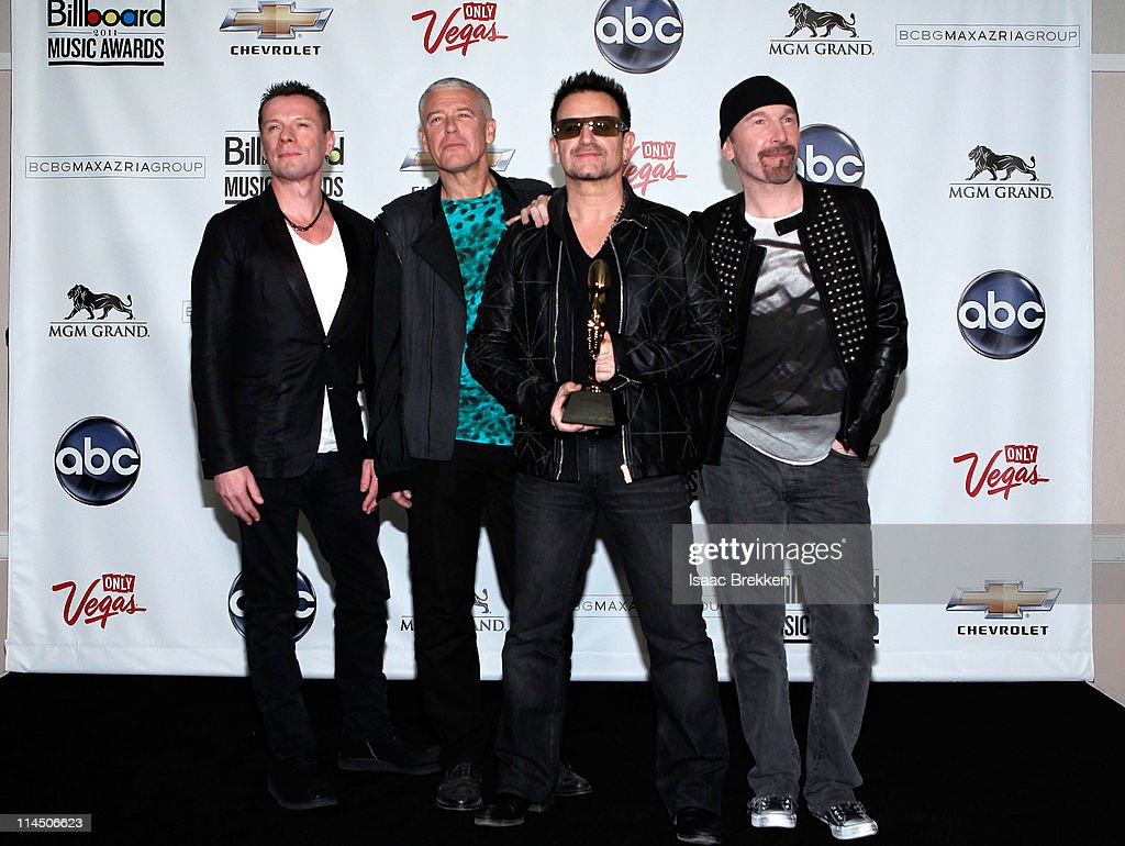 Musicians Larry Mullen Jr Adam Clayton Bono and The Edge pose in the press room with the Touring Top Artist Award during the 2011 Billboard Music...