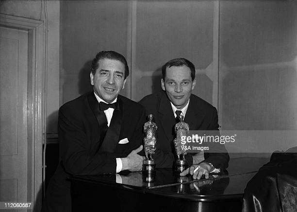 Musicians Mantovani and John Dankworth posed with Ivor Novello awards 1956