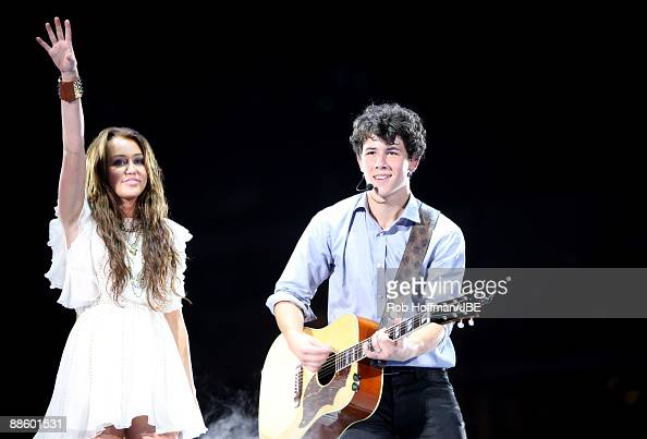 Musicians Miley Cyrus and Nick Jonas of Jonas Brothers perform at New Cowboys Stadium on June 20 2009 in Dallas Texas