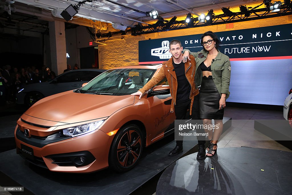 Musicians Nick Jonas and Demi Lovato pose with the 2017 Honda Civic Hatch at the Honda Civic Tour Artists Announcement and Honda Civic North America Launch Event at the Garage on March 22, 2016 in New York City.