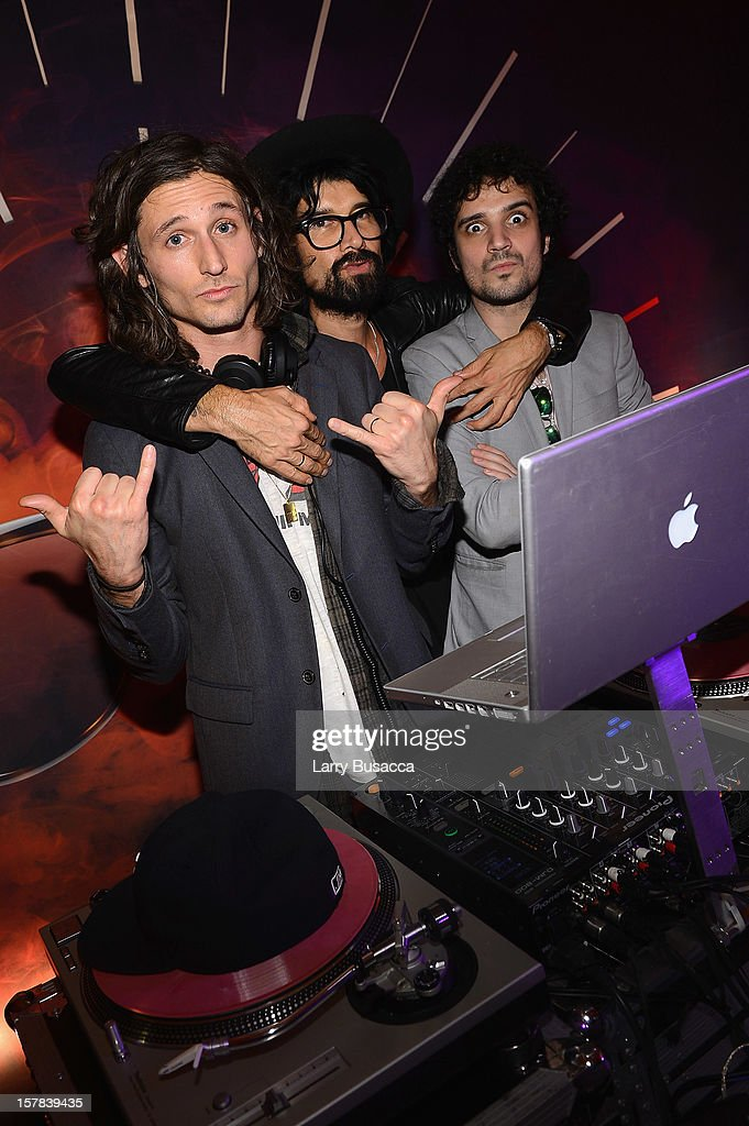 Musicians <a gi-track='captionPersonalityLinkClicked' href=/galleries/search?phrase=Nick+Valensi&family=editorial&specificpeople=651473 ng-click='$event.stopPropagation()'>Nick Valensi</a> (L) and Fabrizio Morett (R) of The Strokes perform with DJ Miles Hendrix (C) during the Carrera Cocktail Party hosted by AD Oasis at The Raleigh on December 6, 2012 in Miami, Florida.