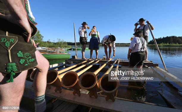 Musicians of the alphorn band 'Holdersberger AlpTraumBläser' prepare to perform on a raft floating on the Elbsee lake near Aitrang southern Germany...