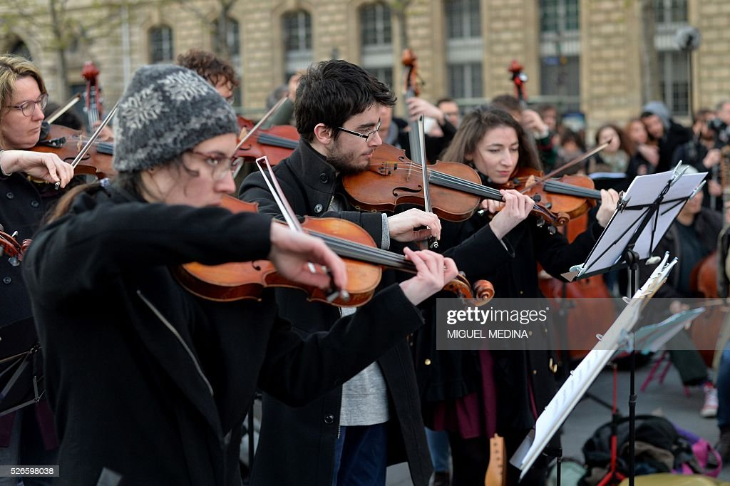 Musicians of the orchestra of classical music 'Standing Musicians' rehearse prior a concert at the Place de la Republique in Paris during the 'Nuit Debout' (Up All Night) movement against the French government's proposed labour reforms on April 30, 2016. / AFP / MIGUEL