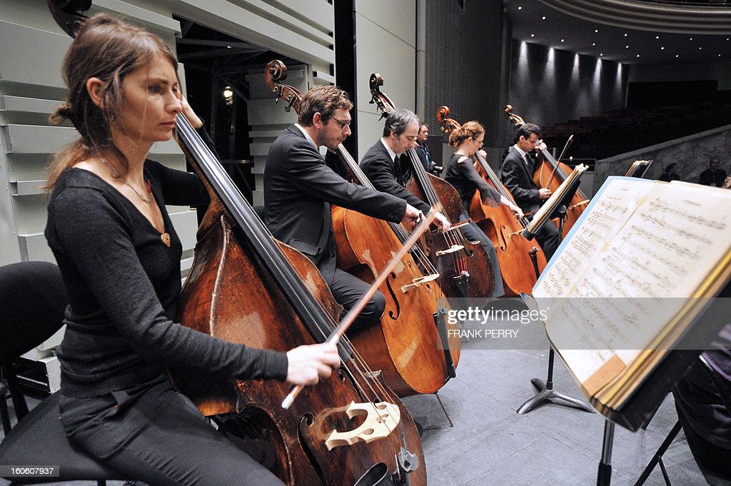 Musicians of the 'Orchestre Lamoureux,' conducted by French Fayçal Karoui, perform Maurice Ravel's Bolero on February 3, 2013, as part of the 'Folle Journee' music festival at the Cite des Congres in Nantes. AFP PHOTO FRANK PERRY