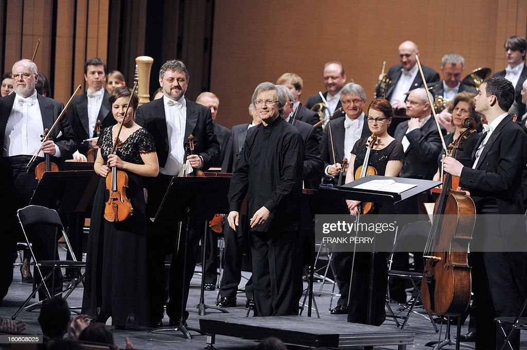 Musicians of the 'Sinfonia Varsovia', conducted by French Jean-Jacques Kantorow (C), aknowledge the audience on February 3, 2013, after a concert as part of the 'Folle Journee' music festival at the Cite des Congres in Nantes.