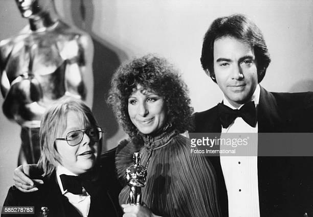 Musicians Paul Williams and Barbra Streisand holding their Oscars for Best Original Song with presenter Neil Diamond at the 49th Academy Awards Los...