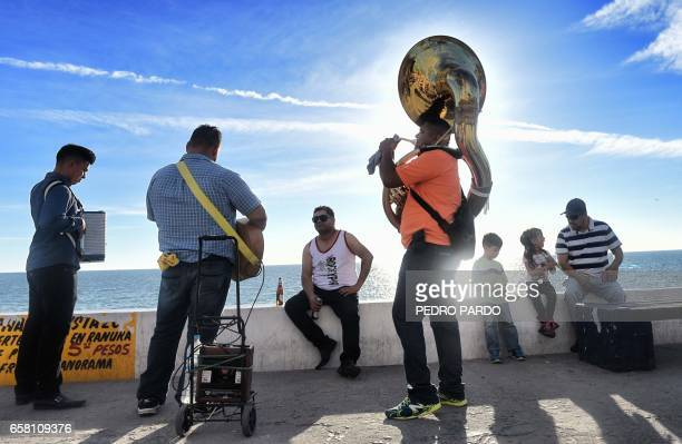 Musicians perform at the Malecon in Puerto Penasco Sonora state Mexico on March 26 2017 / AFP PHOTO / PEDRO PARDO