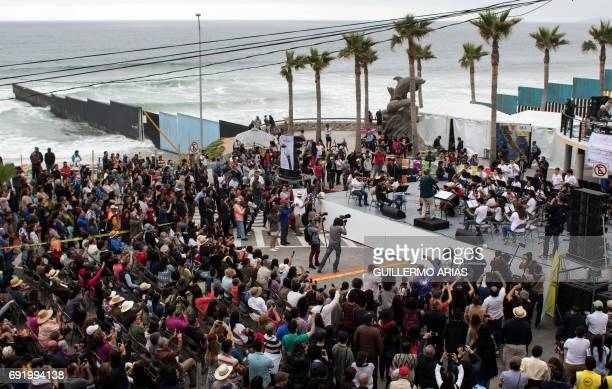 TOPSHOT Musicians perform during the 'Tear Down This Wall' concert at Friendship Park on the Mexican side of the USMexico border in Playas de Tijuana...