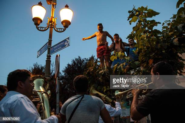 Musicians play for revellers in a tree in the town centre during the Guca Trumpet Festival on August 10 2017 in Guca Serbia Thousands of revellers...