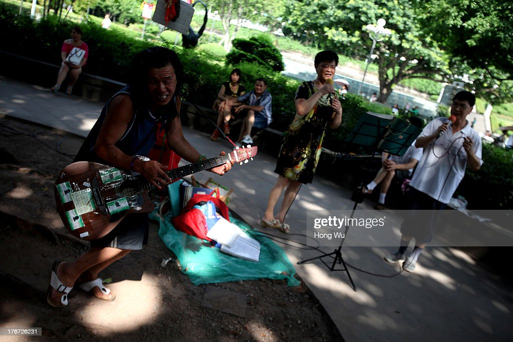 Musicians play instruments and sing in a park on August 4, 2013 in Chongqing, China. Chongqing is a major city in southwest China and became the municipality was created on 14 March 1997. It known as a 'Mountain City' and 'River City' was constructed on the mountain and along the Yangtze River.