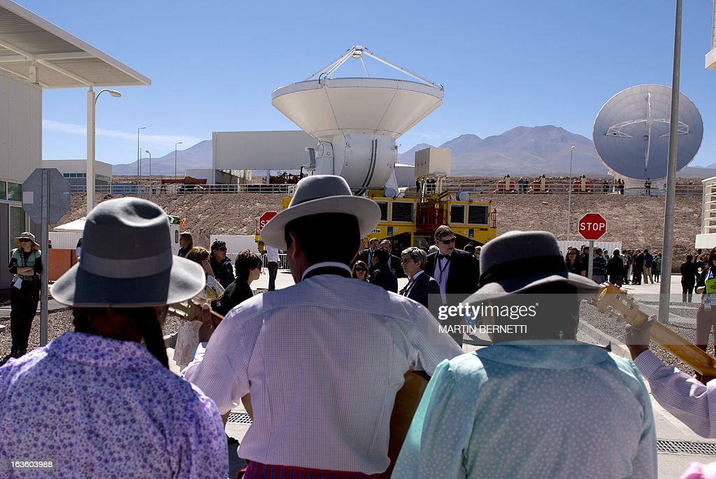 Musicians play with radio telescope antennas of the ALMA (Atacama Large Millimeter/submillimeter Array) project in the background in San Pedro de Atacama , Atacama desert, some 1500 km north of Santiago, on March 13, 2013. The ALMA, an international partnership project of Europe, North America and East Asia with the cooperation of Chile, is presently the largest astronomical project in the world. Today will be opened 59 of 66 high precision antennas, located at 5000 of altitude in the extremely arid Atacama desert. AFP PHOTO/Martin BERNETTI
