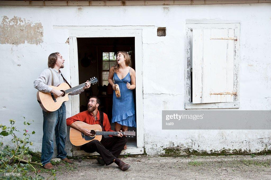 Musicians playing in doorway of run-down building
