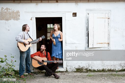 Musicians playing in doorway of run-down building