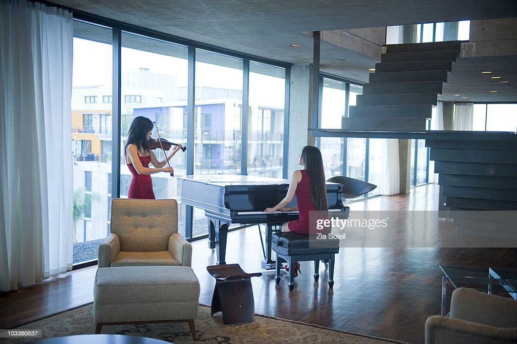 Musicians playing in modern condo : Stock Photo
