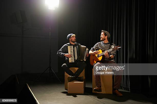 Musicians playing on small stage under spotlight.