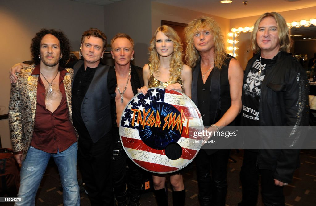 Musicians Rick Savage, Vivian Campbell, Joe Elliott, Phil Collen, and Rick Allen of Def Leppard poses with singer Taylor Swift (3R) during the 2009 CMT Music Awards at the Sommet Center on June 16, 2009 in Nashville, Tennessee.