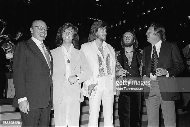 Musicians Robin Barry and Maurice Gibb of the group the Bee Gees pose with Atlantic Records President Ahmet Ertegun and promoter Robert Stigwood at...