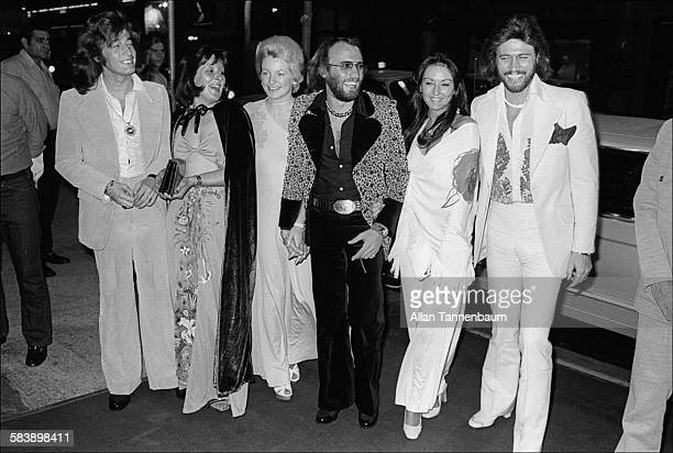Musicians Robin Maurice and Barry Gibb of the group the Bee Gees pose with their wives as they arrive at the group's 20th anniversary party at the...