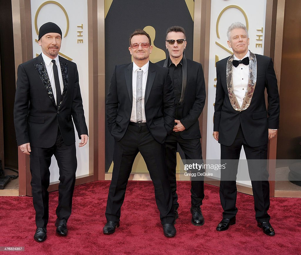 Musicians The Edge Bono Larry Mullen Jr and Adam Clayton of U2 arrive at the 86th Annual Academy Awards at Hollywood Highland Center on March 2 2014...