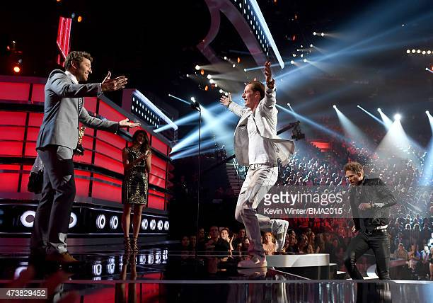 Musicians Tyler Hubbard and Brian Kelley of Florida Georgia Line accept the Top Country Artist award onstage from musician Brett Eldredge during the...