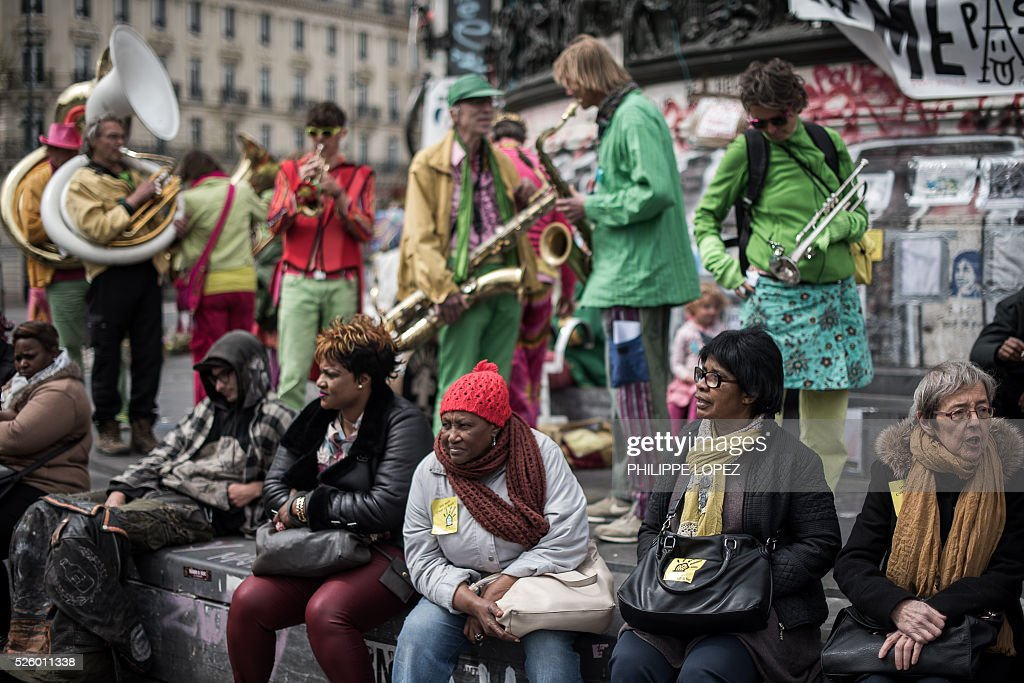 Musicians wearing colourful outfits gather in support of the French Right to Housing association (DAL, 'Droit au Logement') on the Place de la Republique in Paris on April 29, 2016, where the 'Nuit debout' movement has been gathering since March 31. / AFP / PHILIPPE