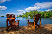 Two Muskoka chairs sitting on a wood dock facing a ake. Across the calm water is a white cottage nestled among green trees. There is a boat dock on the water in front of the cottage.