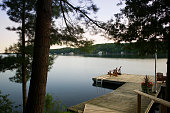 Two Muskoka chairs on a wooden dock facing a calm lake at sunrise
