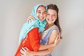 friendship of the religions concept: muslim and christian girl  standing together leaning and smiling at camera
